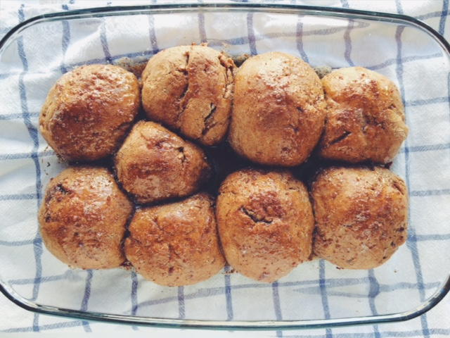 Soft Sourdough cinnamon bread rolls in glass baking dish on a blue and white tea towel