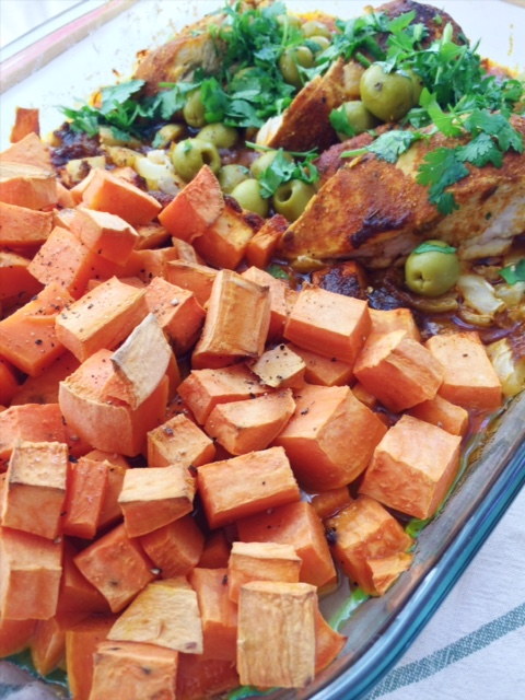 Side view of baked Moroccan chicken with sweet potatoes, cilantro and green olives in a glass baking dish