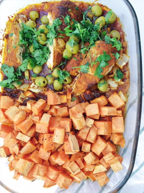 Baked Moroccan Chicken with sweet potatoes topped with cilantro and olives in a glass baking dish
