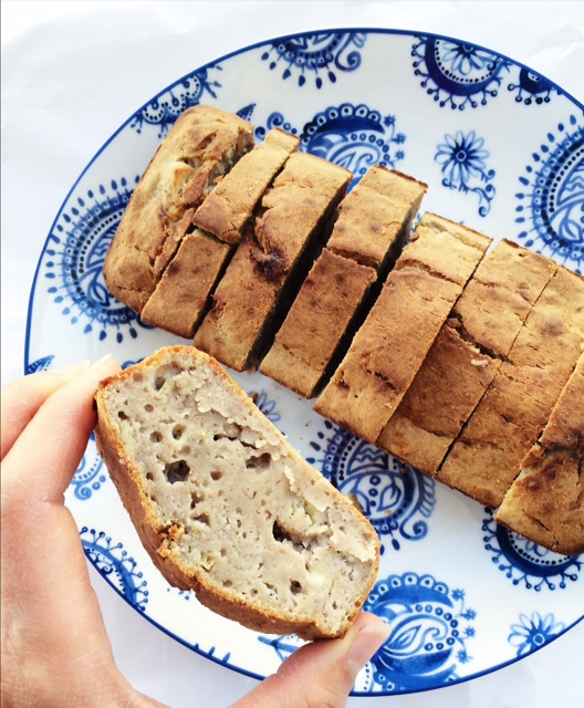 Gluten Free piece of Banana bread heal between fingers in front of bread loaf on a blue and white plate
