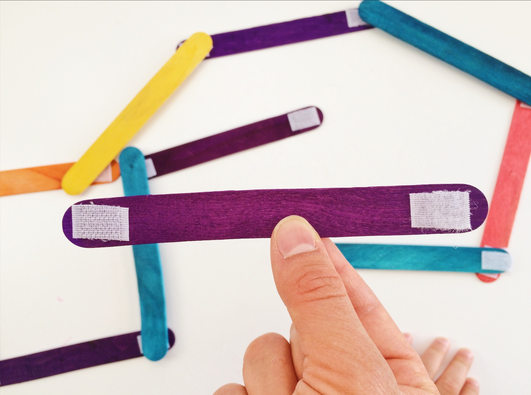 Purple popsicle stick with velcro stuck on either end