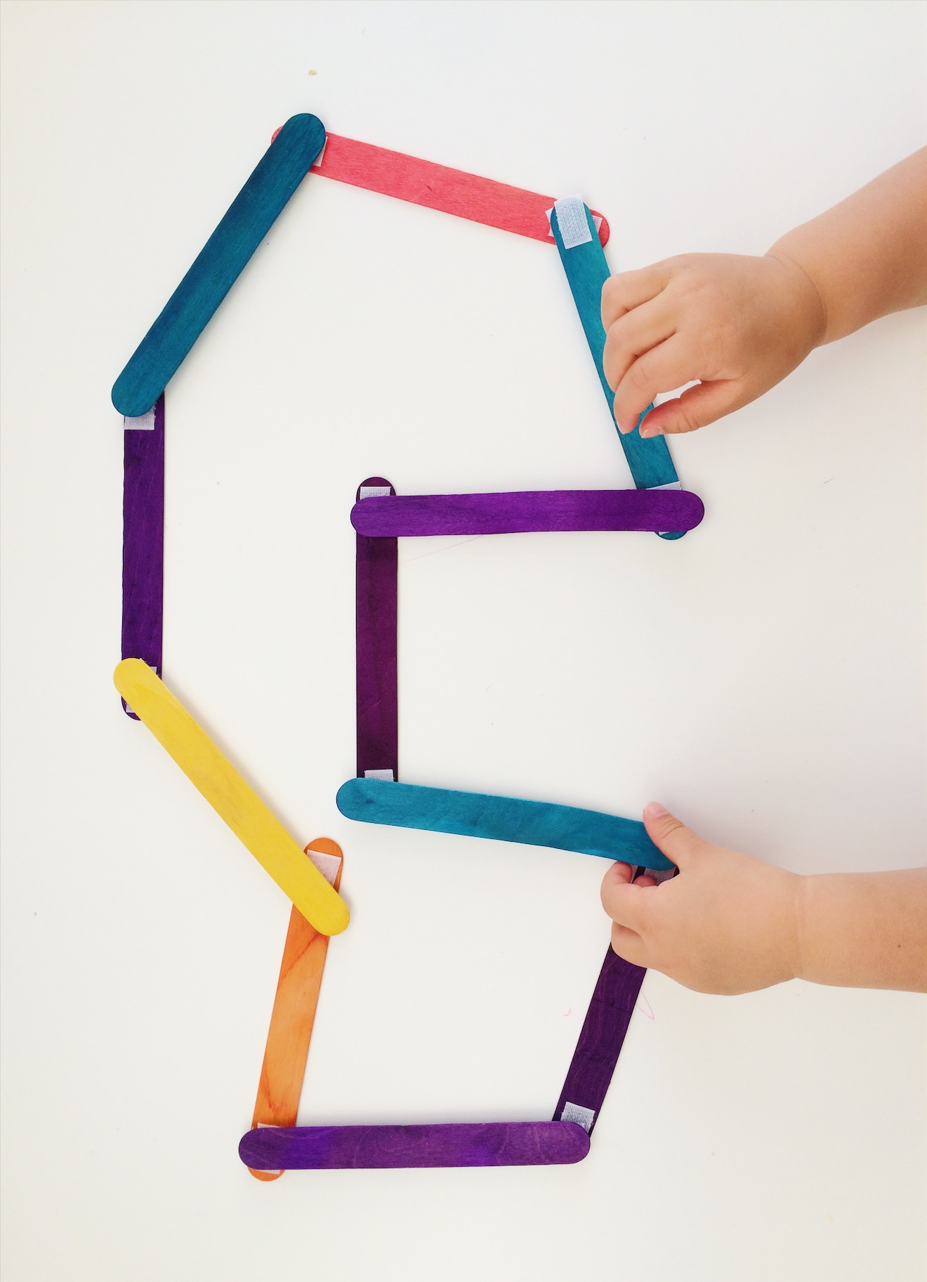Toddler making a shape on white tabel with coloured Popsicle sticks
