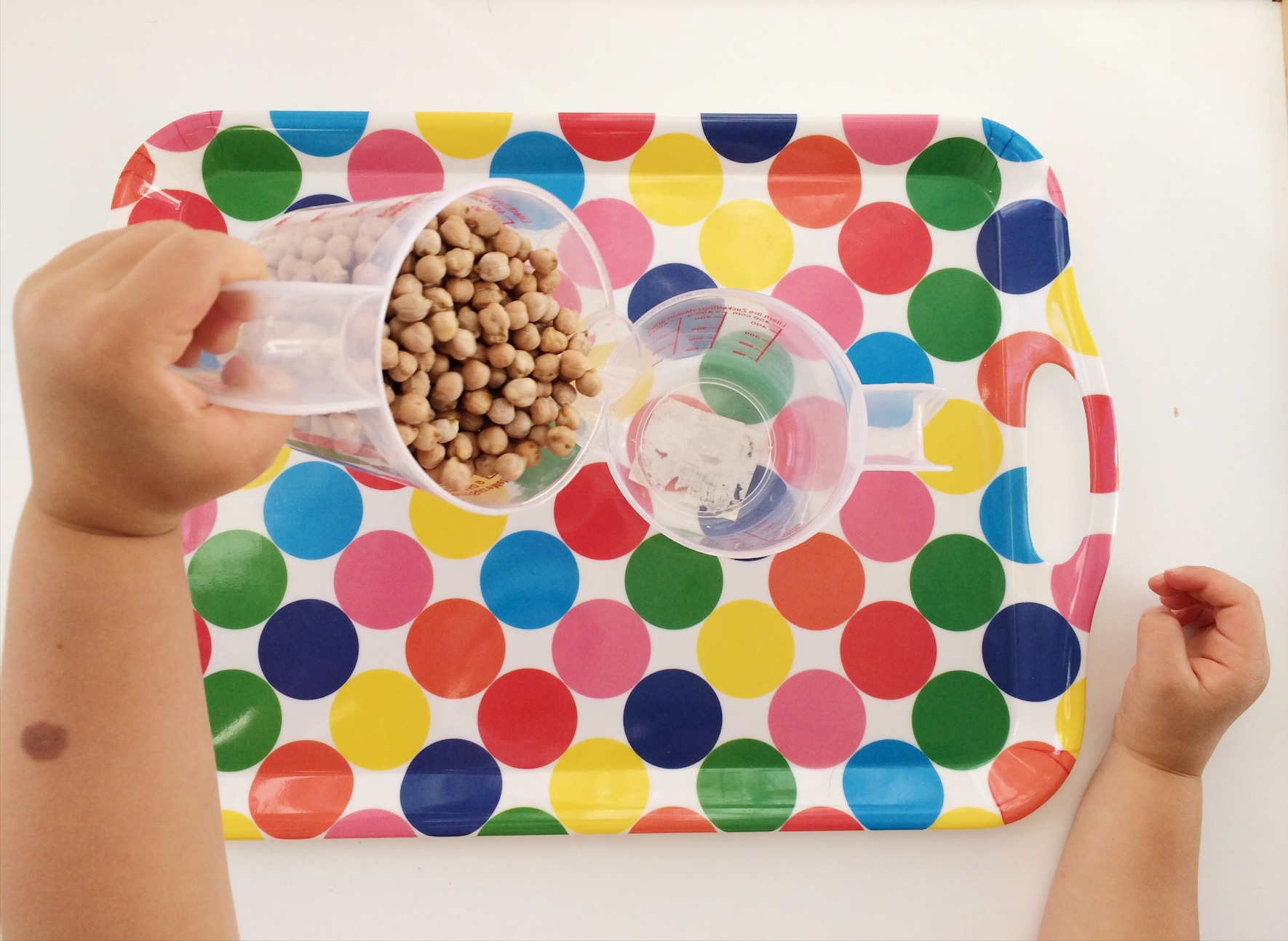 child pouring beans from one jug into another on colourful tray