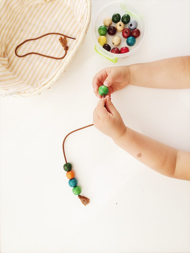 toddler threading beads on brown shoe lace