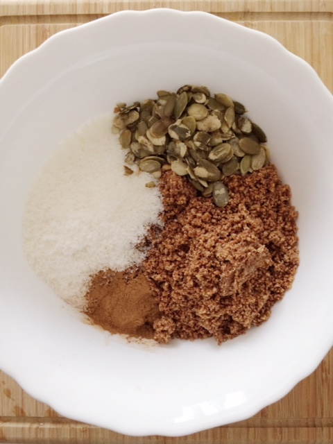 Ground peants, dried shredded coconut, pumpkin seeds and cinnamon in a white mixing bowl