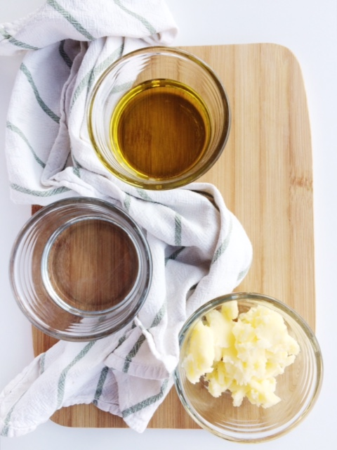 3 small glass cups on a wooden chopping board filled with olive oil, coconut oil and coconut ghee with a striped tea towel interwoven between them