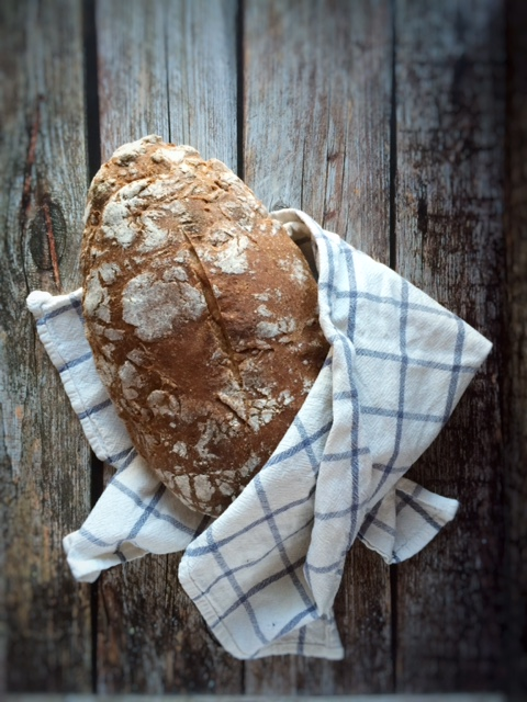 Sourdough loaf of bread wrapped in a kitchen towel on a wooden background, 7 reasons why sourdough bread is the healthiest bread