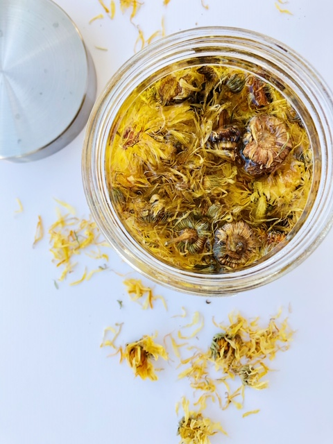 Dried Calendula flowers in olive oil in a glass jar with lid to the side and flower petals around the jar
