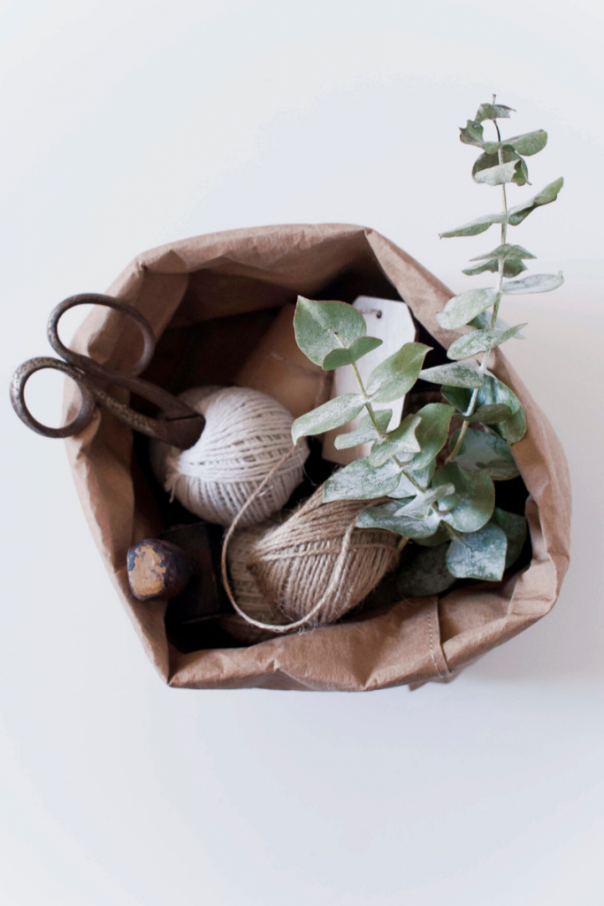 A paper basket filled with scissors, twine and plant leaves