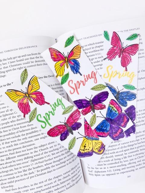 3 handmade bookmarks on an open book