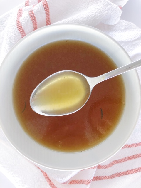 Easy Instant Pot Chicken Stock spoonful of chicken stock over bowl filled with soup