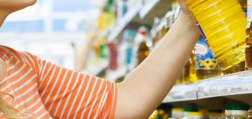 Woman at the supermarket reaching for and holding a bottle of vegetable cooking oil