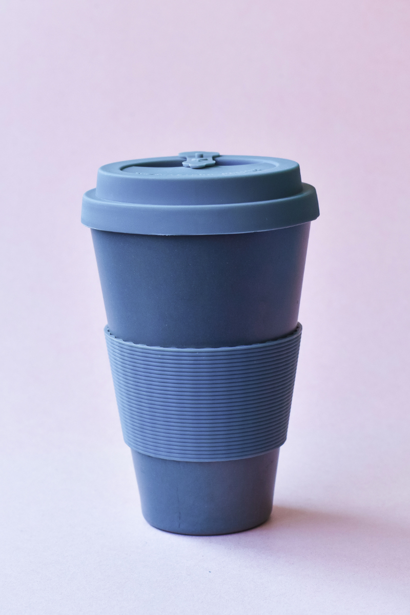 A blue reuasable bamboo coffee cup standing alont with a light purple background