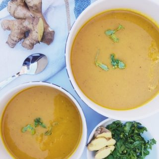 Turmeric and vegetable soup in two bowls spinkeled with cilantro and a bowl of ginger and cilantro on the side