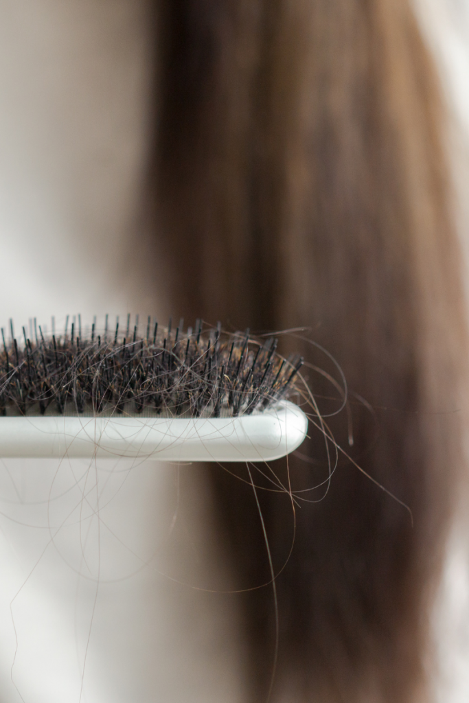 hairbrush with hair in it and woman's long hair in the background