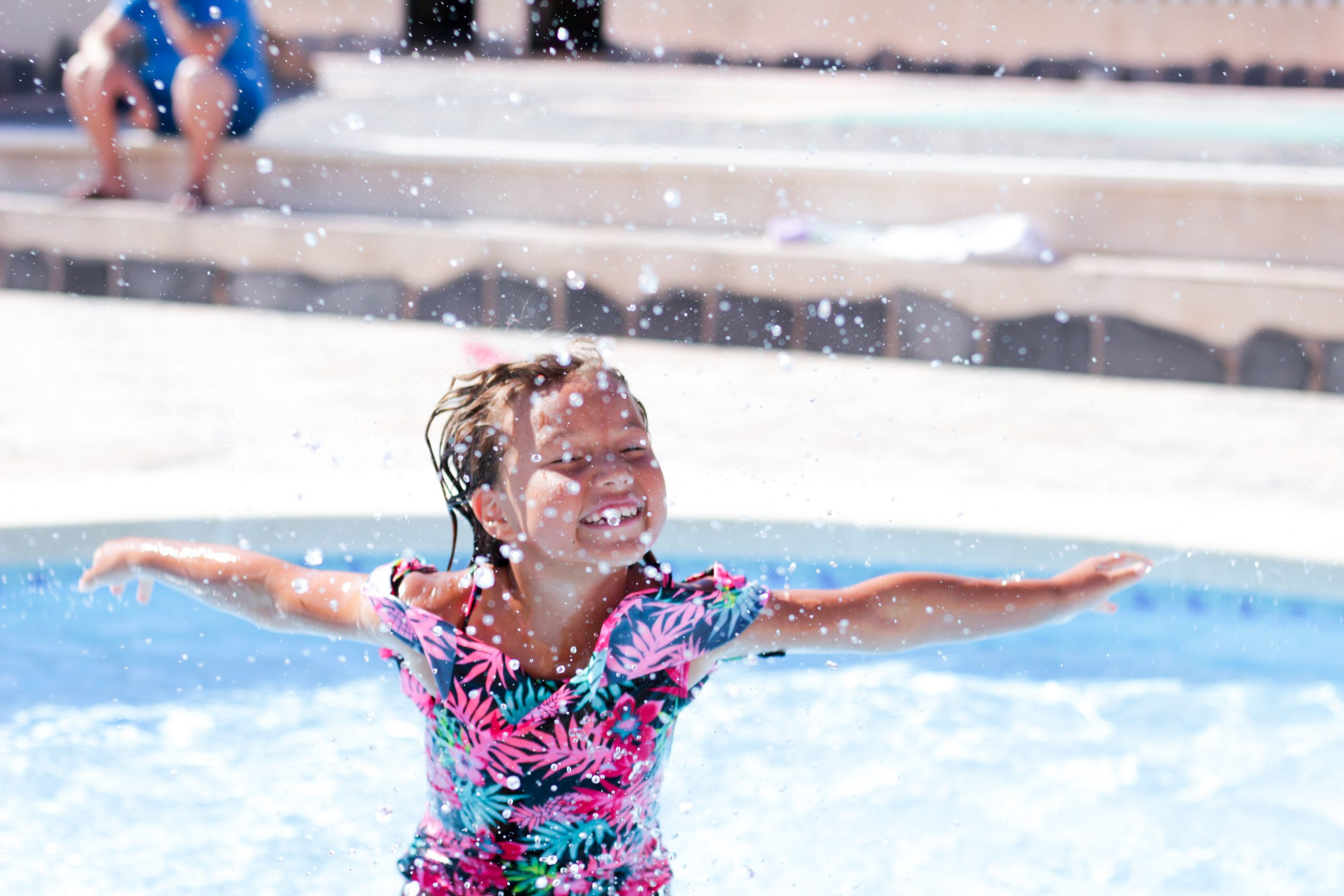 Girl splashing and jumping out of the water in a swimming pool